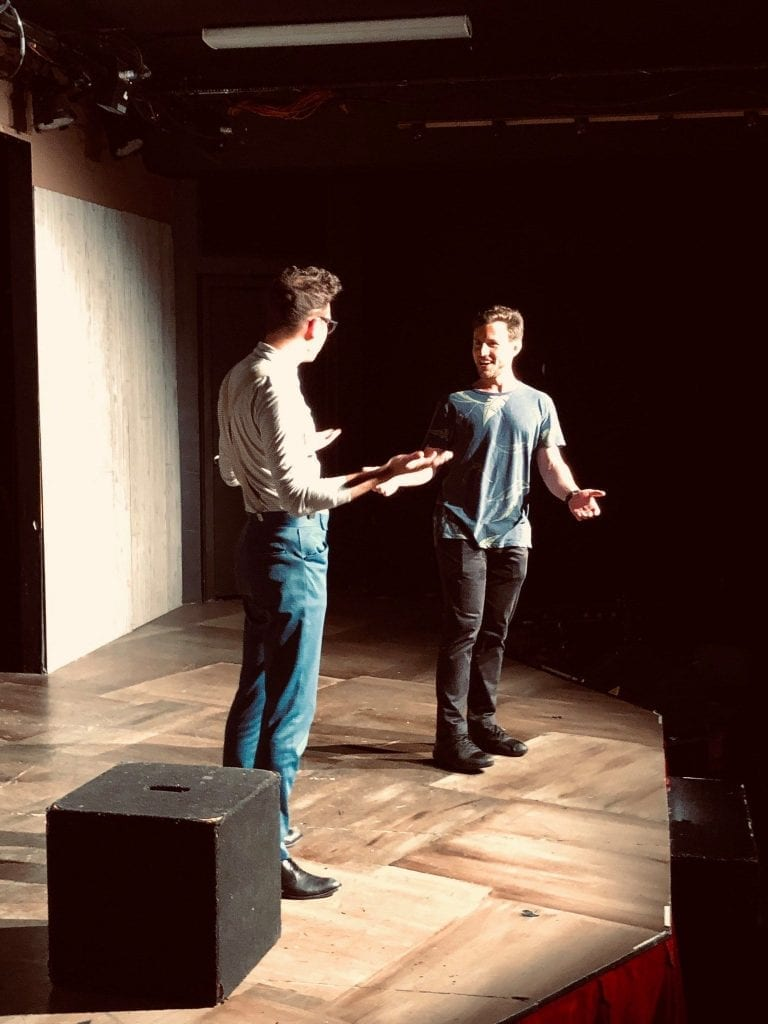 Mike performing improv comedy stage with buddy